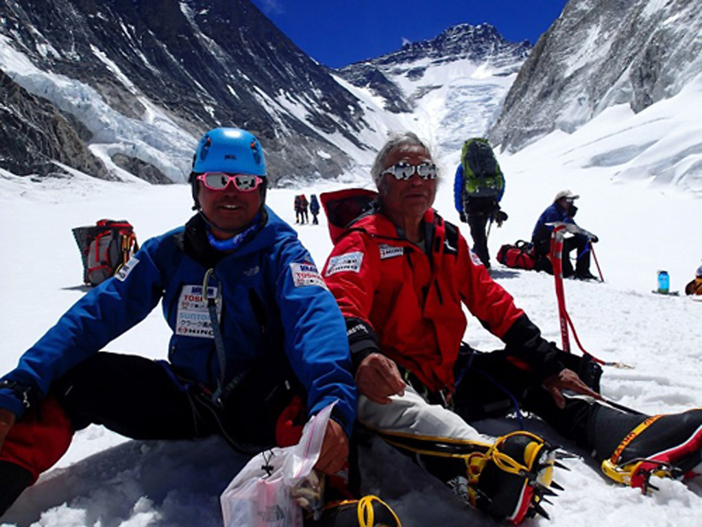 . Eighty-year-old Japanese adventurer Yuichiro Miura, right, and his son, Gota, rest on their way to a camp at 6,500 meters (21,325 feet) from a camp at 6,050 meters (19,849 feet) during their attempt to scale the summit of Mount Everest on May 18, 2013. Miura became the oldest person to reach the world\'s highest peak on Thursday, May 23. (AP Photo/Miura Dolphins)