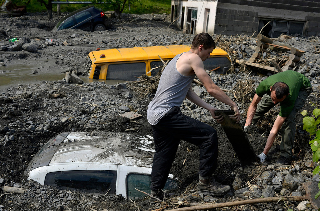 . Residents try to excavate a car trapped in the mud caused by a landslide at the village of Topcic Polje, near the Bosnian town of Zenica, 90 kilometers north of Sarajevo, Bosnia-Herzegovina Tuesday May 20, 2014. Bosnia, Serbia and Croatia have been hit by the worst flooding in more than 100 years, forcing half a million people out of their homes and leading to more than three dozen deaths. (AP Photo/Sulejman Omerbasic)