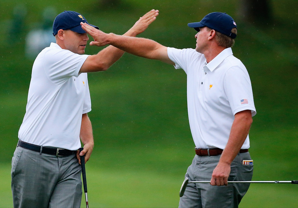 . Steve Stricker (L) and Bill Haas of the U.S. Team celebrate winning the 14th hole during the weather-delayed Day Three Foursome Matches at the Muirfield Village Golf Club on October 6, 2013  in Dublin, Ohio.  (Photo by Matt Sullivan/Getty Images)