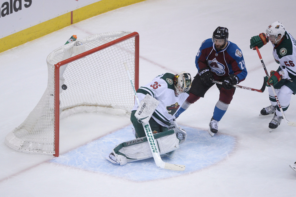 . A shot by Jamie McGinn (11) of the Colorado Avalanche slips into the net past Darcy Kuemper (35) of the Minnesota Wild during the first period of action. At right are Maxime Talbot (25) of the Colorado Avalanche and Erik Haula (56) of the Minnesota Wild.   (Photo by Karl Gehring/The Denver Post)