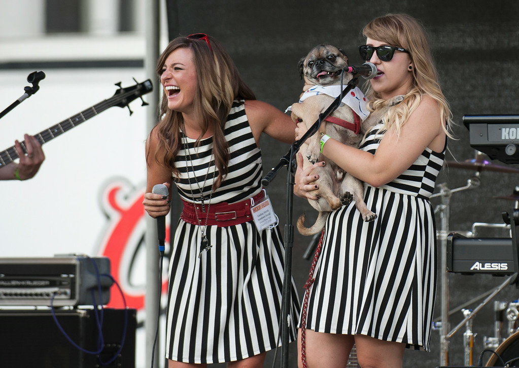 . Sundown Social band members Lindsay Smith (L), and Nikki Smith (R), holding a pug named Elvis Pugsley, perform  at Woof Fest! in downtown Denver, Colorado, Sunday, August 17, 2014. The free festival included two music stages, food trucks, and space for pets and their owners to play. ((Photo By Brenden Neville/Special to The Denver Post))
