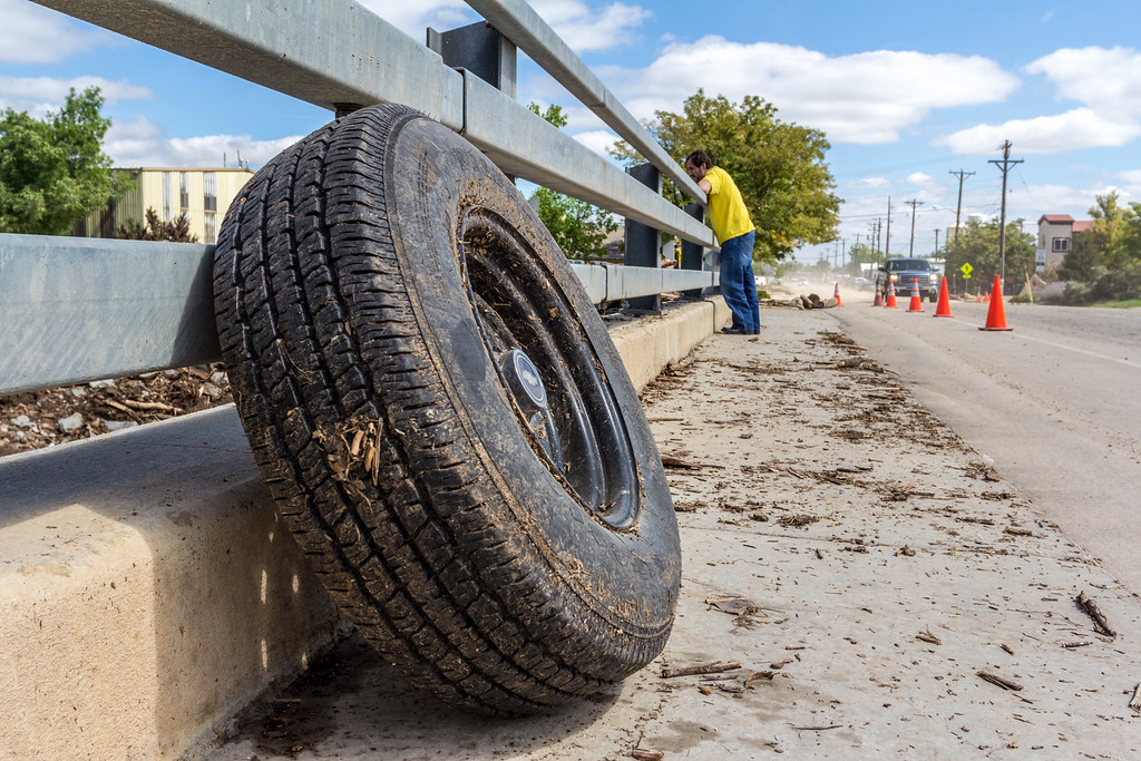 . A wheel and tire from a Chevrolet vehicle, caught in the rising St. Vrain Creek in Longmont, is placed on an overpass covered in dirt, dust, and debris as Andy Frith, an employee of a Longmont business, observes the rapids underneath. Foot and bicycle traffic, normally permitted under the bridge, is not possible and is blocked by police lines. Photo by Arien Talabac