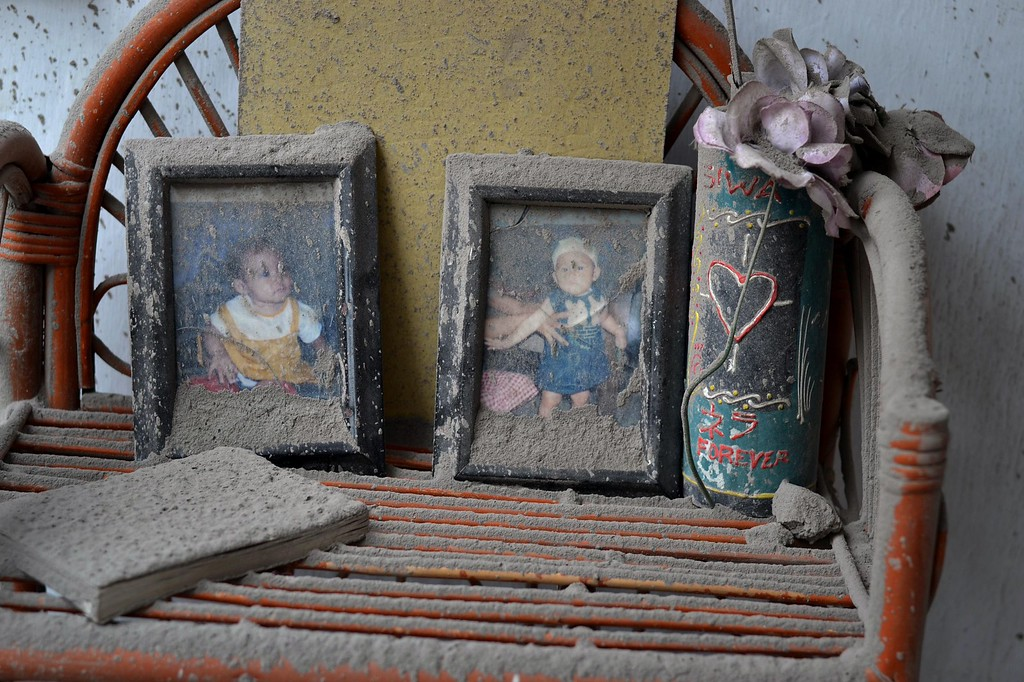 . Family photographs are covered by ash inside a house damaged by heavy ashfall in Malang, East Java on February 16, 2014 following the volcanic eruption of Mount Kelud in East Java on February 13. AFP PHOTO / Aman ROCHMAN/AFP/Getty Images