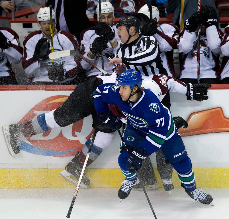. Colorado Avalanche\'s Ryan Wilson, middle, collides with linesman Lonnie Cameron while trying to check Vancouver Canucks\' Shawn Matthias during the third period of an NHL hockey game Thursday, April 10, 2014, in Vancouver, British Columbia. (AP Photo/The Canadian Press, Darryl Dyck)