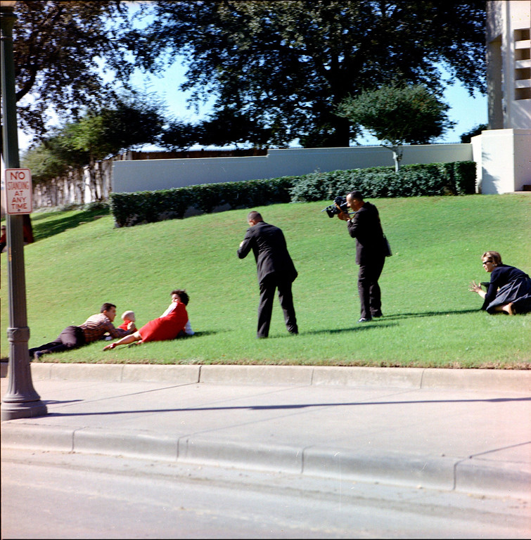. Frightened onlookers cover their children on the grass in the plaza as cameramen record their actions. Cecil Stoughton/John F. Kennedy Presidential Library and Museum