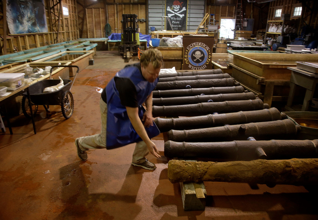 . Chris Macort, a field archeologist working with the Whydah pirate ship museum, reaches down to check one of the ships cannons at the museum\'s warehouse in Brewster, Mass., Tuesday, Sept. 17, 2013. The Whydah sank in a brutal storm in 1717 with plunder from 50 ships. It was discovered in 1984. (AP Photo/Stephan Savoia)