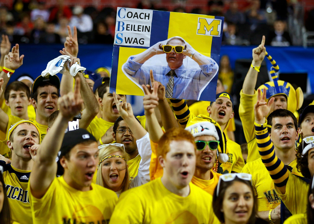 . Michigan Wolverines fans hold a sign with a picture of head coach John Beilein as they celebrate ahead of the NCAA men\'s Final Four championship basketball game against the Louisville Cardinals in Atlanta, Georgia April 8, 2013.   REUTERS/Jeff Haynes
