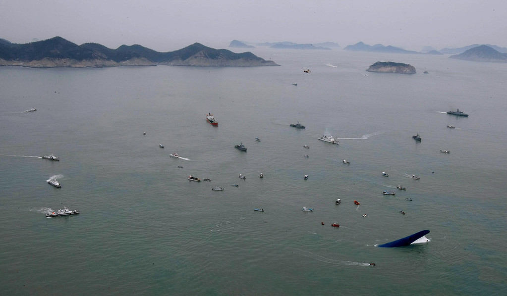 . This aerial photo taken at sea some 20 kilometers off the island of Byungpoong in Jindo on April 16, 2014 shows South Korea Coast Guard members searching for passengers near a South Korean ferry (bottom R) that capsized on its way to Jeju island from Incheon. South Korean rescue teams, including elite navy SEAL divers, raced on April 16 to find up to 293 people missing from a capsized ferry carrying 459 passengers and crew -- mostly high school students bound for a holiday island.   AFP PHOTO/YONHAPYONHAP/AFP/Getty Images