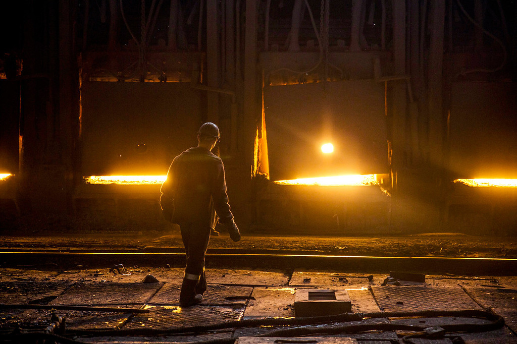 . An employee walks past the scrap metal furnace inside the Zaporizhstal steel plant, owned and operated by Metinvest BV, at their site in Zaporizhzhya, Ukraine, on Monday, Oct. 14, 2013. Metinvest BV, Ukraine\'s largest steelmaker, last year acquired 49.9% in steelmaker Zaporizhstal a manufacturer of semi-finished steel products, including hot and cold-rolled plates and coils. Photographer: Vincent Mundy/Bloomberg