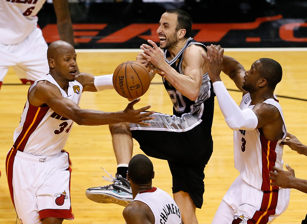 . Manu Ginobili #20 of the San Antonio Spurs loses the ball as he drives between Ray Allen #34 and Dwyane Wade #3 of the Miami Heat in overtime during Game Six of the 2013 NBA Finals at AmericanAirlines Arena on June 18, 2013 in Miami, Florida.  (Photo by Kevin C. Cox/Getty Images)