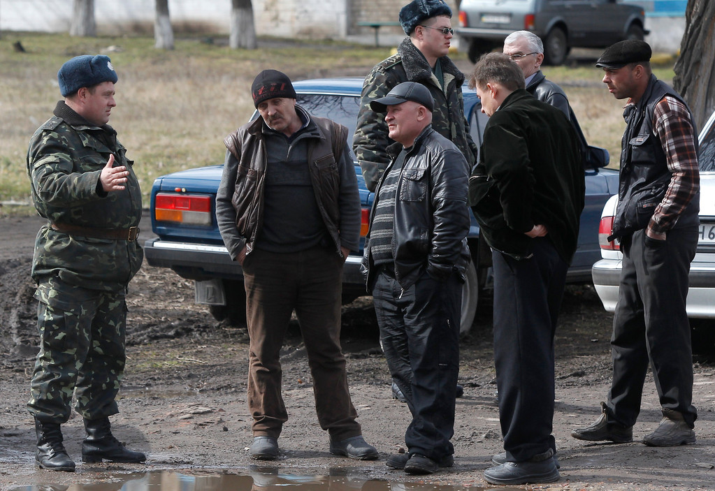 . A Ukrainian officer talks with a pro Russian activist in their camp near the armory Ukrainian army where they stand to prevent the export of arms and ammunition in the village of Poraskoveyevka, eastern Ukraine, Thursday, March 20, 2014. (AP Photo/Sergei Grits)