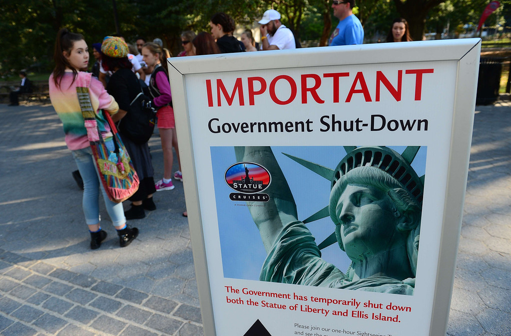 . Tourists walk by a sign announcing that the Statue of Liberty is closed due to a US government shutdown in New York, October 1, 2013. AFP PHOTO/Emmanuel DUNAND/AFP/Getty Images
