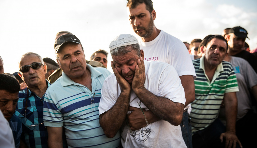 ". YAHUD MONOSON, ISRAEL - JULY 16:  Mourners weep for Dror Khenin during his funeral on July 16, 2014 in Yahud Monoson, Israel. Yesterday Khenin was the first Israeli to be killed by a Hamas mortar as he offered food to Israeli soldiers working near the Erez border crossing between Israel and Gaza. As Operation ""Decisive Edge\"" enters its ninth day, over 200 Palestinians have been killed in Israeli missile strikes.  (Photo by Andrew Burton/Getty Images)"