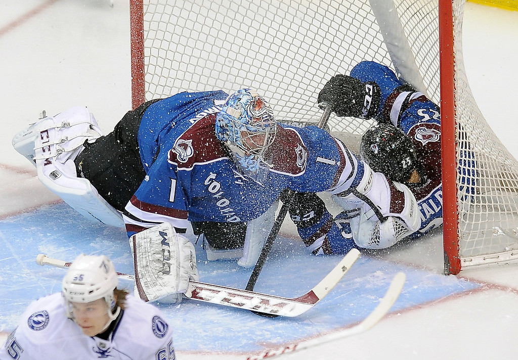 . Colorado Avalanche center Maxime Talbot, right, slides into the goal past Avalanche goalie Semyon Varlamov, left, of Russia, in the first period of an NHL hockey game against the Tampa Bay Lightning, Sunday, March 2, 2014 in Denver. (AP Photo/Chris Schneider)