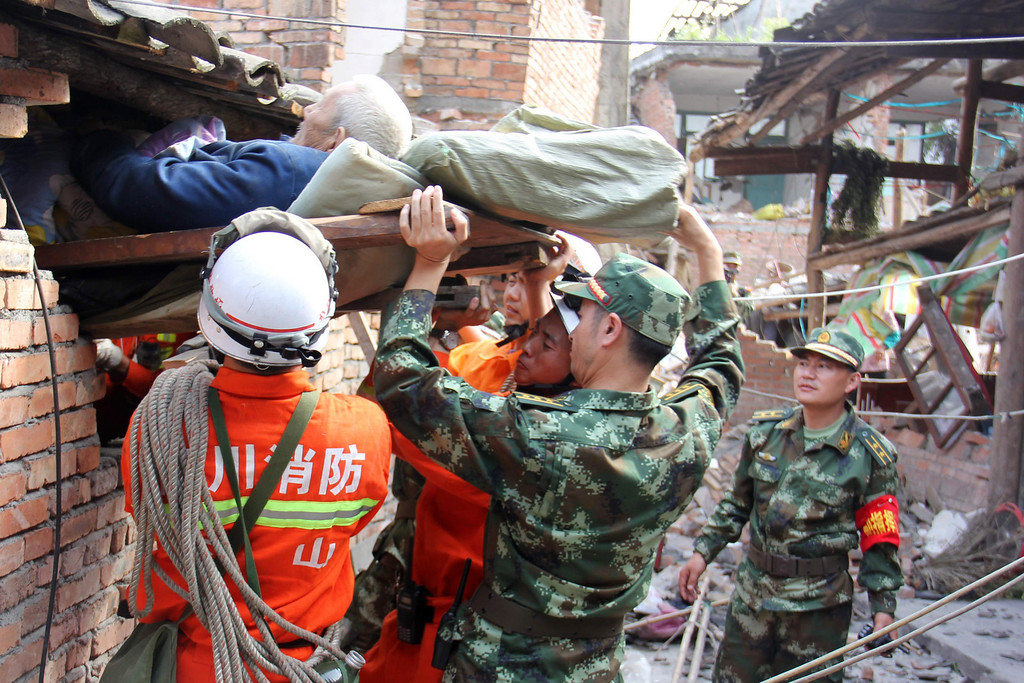 . Rescuers carry a paralysed elderly person from his damaged house in Qingren township in seriously damaged Lushan county after a shallow earthquake at magnitude 7.0  hit the city of Ya\'an, in southwest China\'s Sichuan province on April 20, 2013. More than 150 people were killed and 5,700 injured when a strong earthquake hit a mountainous part of southwestern China on April 20, destroying thousands of homes and triggering landslides. AFP/Getty Images