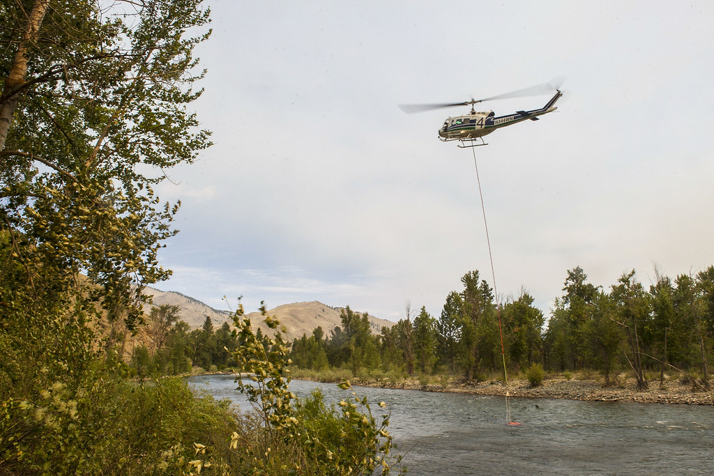 . A helicopter refills with water in the Methow River onSunday,  July 20, 2014, in Carlton, Washington. The Carlton Complex fires have swept the region covering over 215,000 acres of land and destroying over 100 structures. Fire crews have been called in from all over the country in order to help contain the fire.  (AP Photo/The Seattle Times, Maddie Meyer)