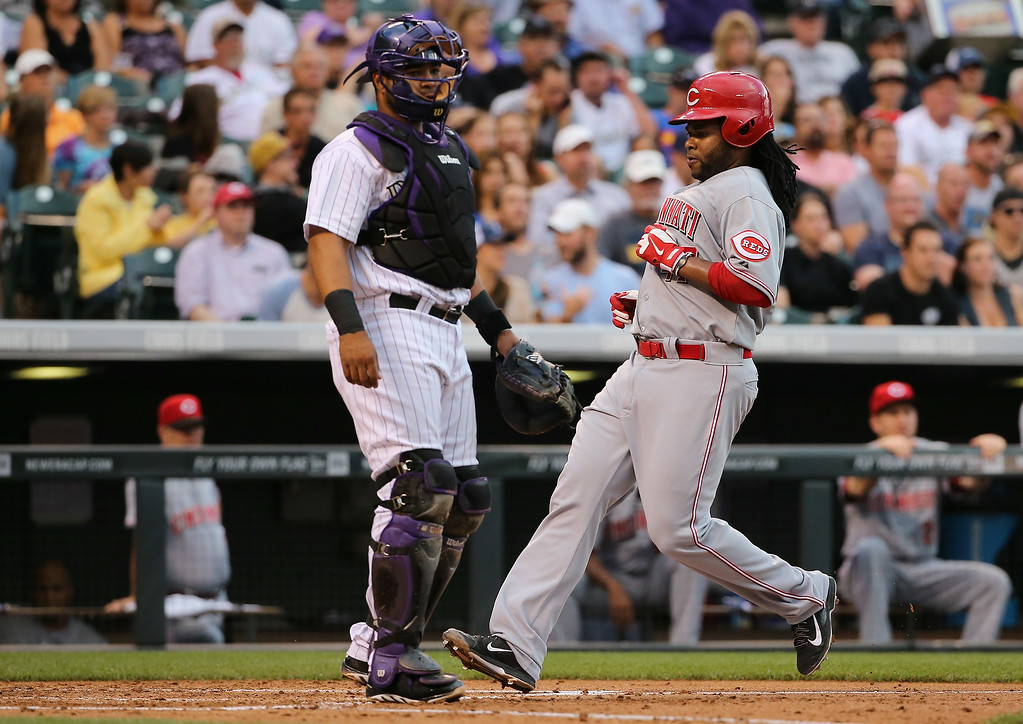 . DENVER, CO - AUGUST 15:  Johnny Cueto #47 of the Cincinnati Reds scores on a ground ball by Jay Bruce #32 of the Cincinnati Reds as catcher Wilin Rosario #20 of the Colorado Rockies looks on and the Reds tie the score 1-1 in the third inning at Coors Field on August 15, 2014 in Denver, Colorado.  (Photo by Doug Pensinger/Getty Images)