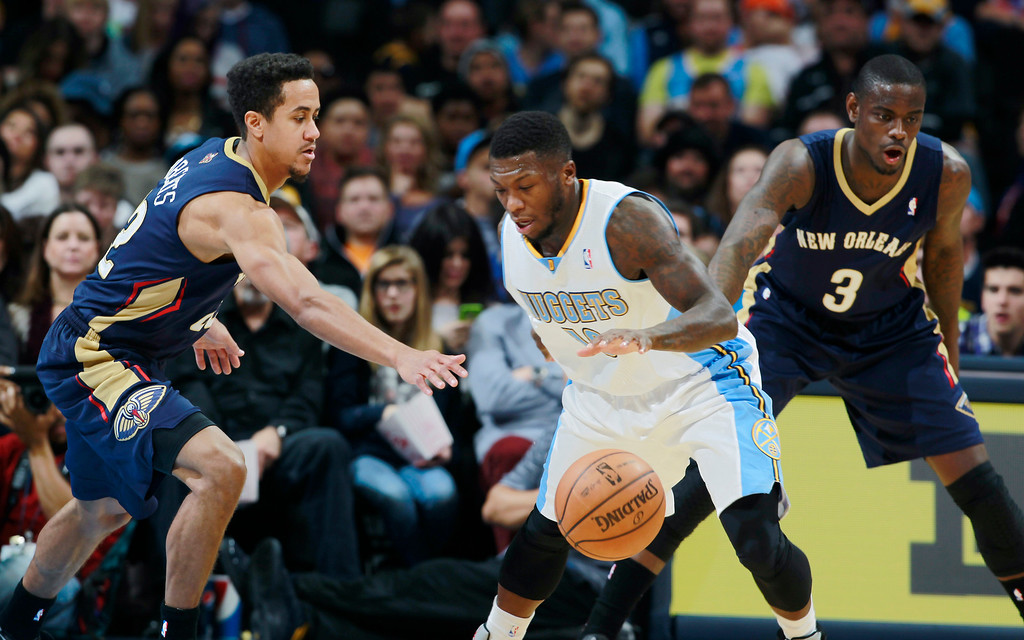 . Denver Nuggets guard Nate Robinson, center, picks up a loose ball as New Orleans Pelicans guards Brian Roberts, left, and Anthony Morrow cover in the third quarter of the Nuggets\' 102-93 victory in an NBA basketball game in Denver on Sunday, Dec. 15, 2013. (AP Photo/David Zalubowski)