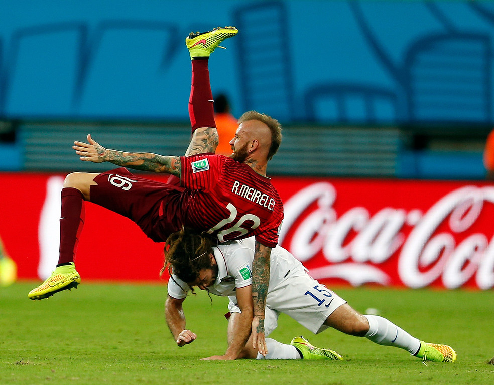 . Portugal\'s Raul Meireles falls on top of United States\' Kyle Beckerman during the group G World Cup soccer match between the United States and Portugal at the Arena da Amazonia in Manaus, Brazil, Sunday, June 22, 2014. (AP Photo/Julio Cortez)