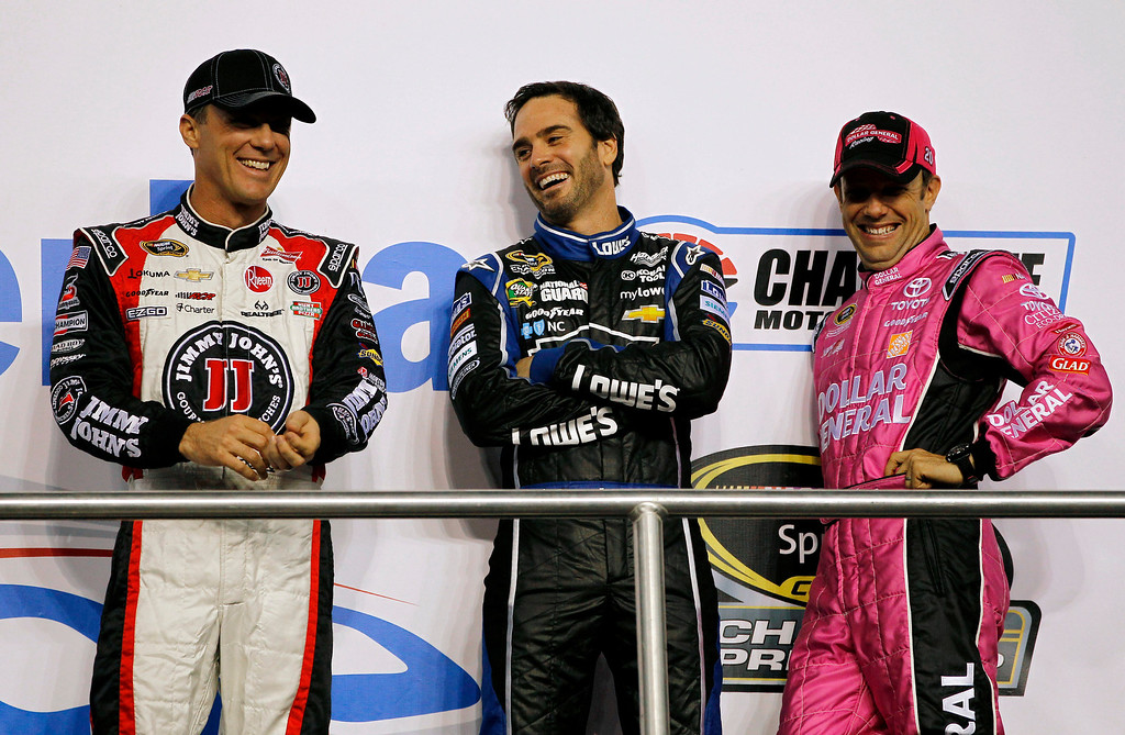 . Kevin Harvick, left, Jimmie Johnson and Matt Kenseth, right, chat during driver introductions before the NASCAR Sprint Cup Series auto race at Charlotte Motor Speedway in Concord, N.C., Saturday, Oct. 12, 2013. (AP Photo/Terry Renna)