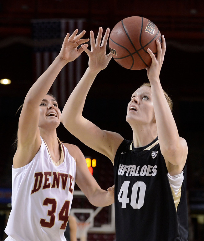 . University of Colorado\'s Rachel Hargis takes a shot over Theresa Wirth during a games against the University of Denver on Tuesday, Dec. 11, at the Magnus Arena on the DU campus in Denver.   (Jeremy Papasso/Daily Camera)