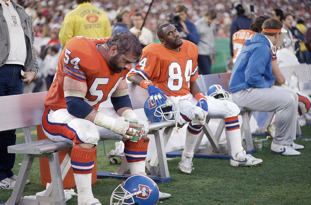 . Denver Broncos Ricky Nattiel (84) and Keith Bishop (54) sit dejectedly on the bench during second quarter of Super Bowl when the Washington Redskins scored a record-setting 35 points, Sunday, Jan. 31, 1988 in San Diego. (AP Photo/Ed Andrieski)