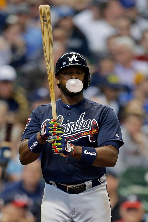 . Atlanta Braves\' Justin Upton blows a bubble as he bats against the Milwaukee Brewers in the sixth inning of an opening day baseball game Monday, March 31, 2014, in Milwaukee. (AP Photo/Jeffrey Phelps)