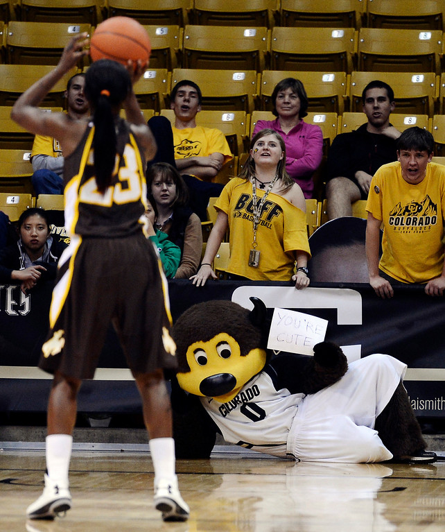 . Colorado mascot Chip holds a sign while trying to distract Wyoming\'s Chelan Landry as she shoots a free throw during their NCAA college basketball game, Wednesday, Nov. 28, 2012, in Boulder, Colo. Colorado won 68-59. (AP Photo/The Daily Camera, Jeremy Papasso)