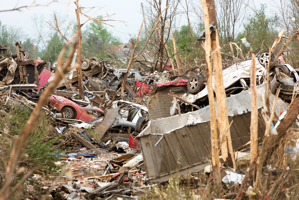 . Piles of cars and the scattered remnants of homes and buildings are in a ditch in Vilonia, Ark., Monday, April 28, 2014 after a tornado struck the town late Sunday.  (AP Photo/Karen E. Segrave)