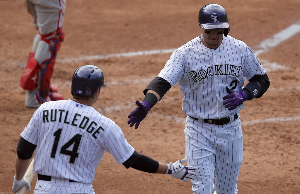 . Troy Tulowitzki #2 of the Colorado Rockies is welcomed home by Josh Rutledge #14 after scoring on an RBI single by Nolan Arenado #28 of the Colorado Rockies off of Roberto Hernandez #27 of the Philadelphia Phillies to take a 4-3 lead in the third inning at Coors Field on April 20, 2014 in Denver, Colorado.  (Photo by Doug Pensinger/Getty Images)