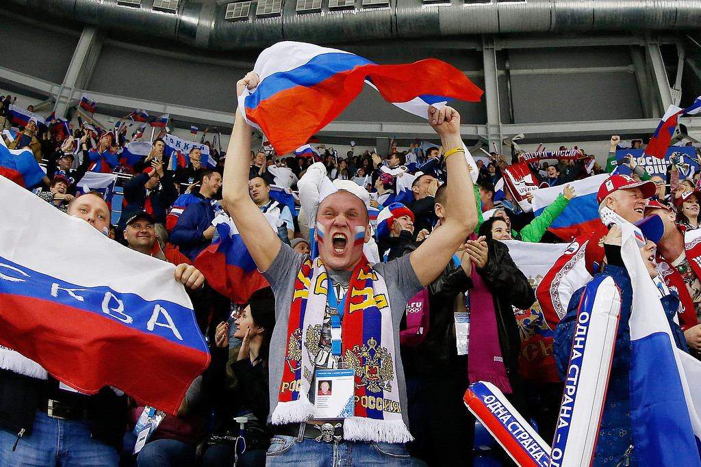 . A Russian hockey fan celebrates Alyona Khomich\'s goal against Sweden during the 2014 Winter Olympics women\'s ice hockey game at Shayba Arena, Thursday, Feb. 13, 2014, in Sochi, Russia. (AP Photo/Petr David Josek)