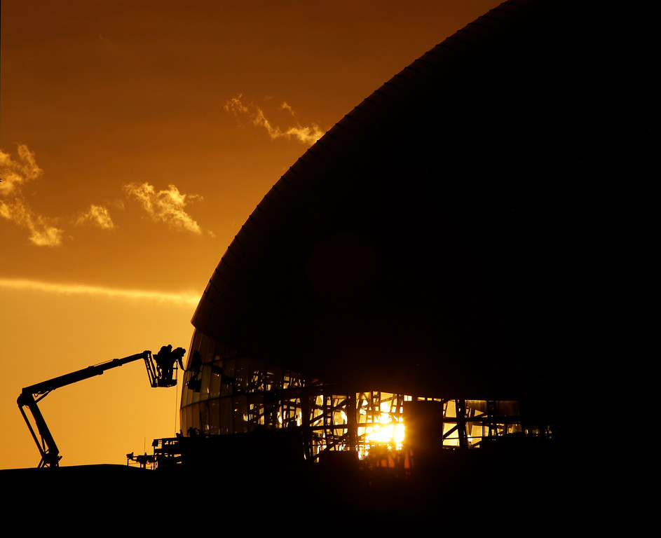 . A worker cleans windows at the Bolshoy Ice Dome at sunset as preparations continue for the 2014 Winter Olympics, Wednesday, Feb. 5, 2014, in Sochi, Russia. (AP Photo/Charlie Riedel)