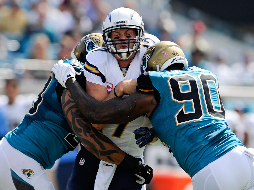 . San Diego Chargers quarterback Philip Rivers, center, grimaces as he is caught between Jacksonville Jaguars defensive end Jason Babin, left, and defensive end Andre Branch (90) after throwing a pass in the first half of an NFL football game in Jacksonville, Fla., Sunday, Oct. 20, 2013.(AP Photo/Stephen Morton)