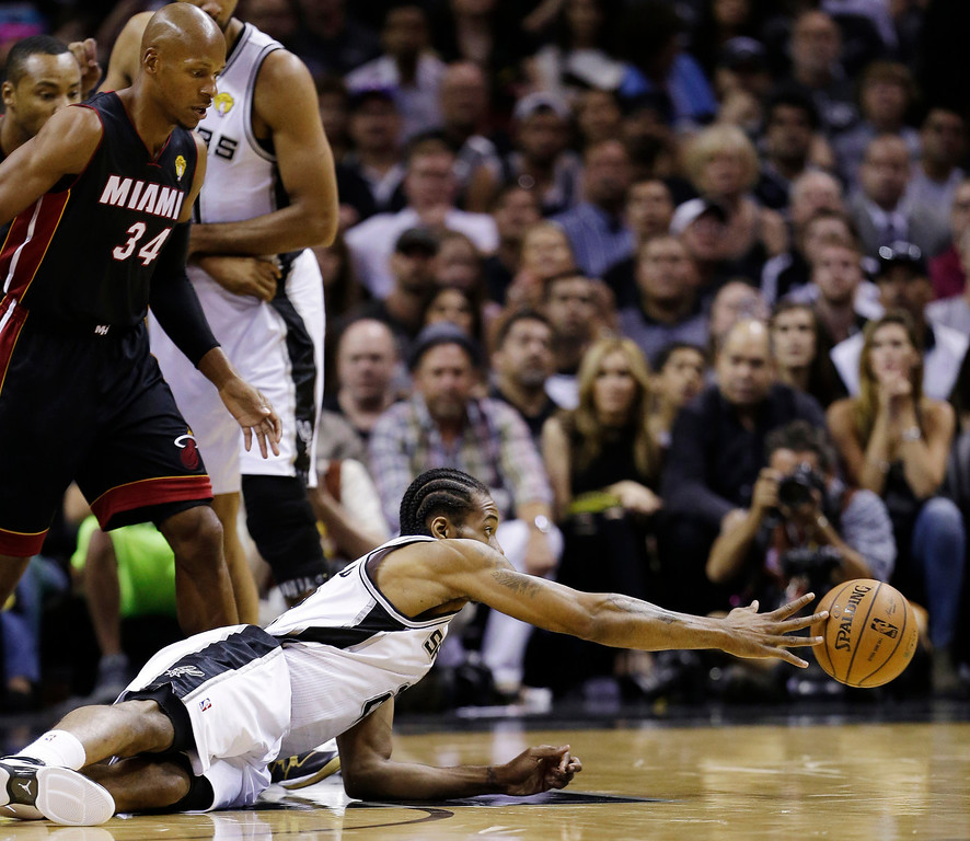 . San Antonio Spurs forward Kawhi Leonard passes the ball after hitting the floor as Miami Heat guard Ray Allen (34) looks on during the first half in Game 5 of the NBA basketball finals on Sunday, June 15, 2014, in San Antonio. (AP Photo/David J. Phillip)