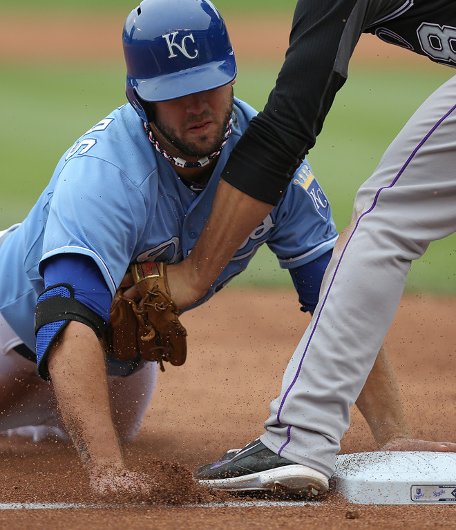 . KANSAS CITY, MO - MAY 14:  Mike Moustakas #8 of the Kansas City Royals is tagged out by Nolan Arenado #28 of the Colorado Rockies as he tries to steal in the second inning at Kauffman Stadium on May 14, 2014 in Kansas City, Missouri. (Photo by Ed Zurga/Getty Images)