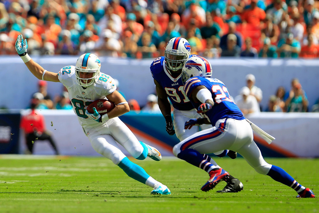 . (L)  Brian Hartline #82 of the Miami Dolphins rushes with ball while being pressured by (C)  Manny Lawson #91 of the Buffalo Bills and (R)  Aaron Williams #23 of the Buffalo Bills at Sun Life Stadium on October 20, 2013 in Miami Gardens, Florida.  (Photo by Chris Trotman/Getty Images)