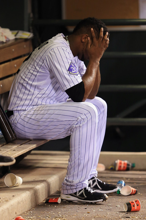 . DENVER, CO - AUGUST 10:  Starting pitcher Juan Nicasio #12 of the Colorado Rockies sits in the dugout after being removed from the game by manager Walt Weiss of the Rockies against the Pittsburgh Pirates in the sixth inning at Coors Field on August 10, 2013 in Denver, Colorado.  (Photo by Doug Pensinger/Getty Images)