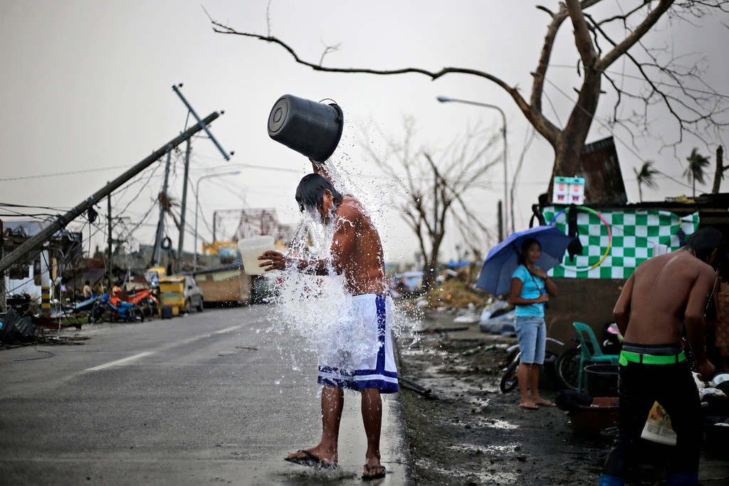 . A Filipino youth takes a shower on the side of a road at a neighborhood devastated by Typhoon Haiyan in Tacloban, Philippines, Thursday, Nov. 21, 2013.  (AP Photo/Dita Alangkara)