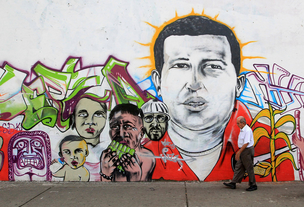 . A man walks in front of a wall bearing the image of the late Venezuelan President Hugo Chavez in Cali March 6, 2013. Supporters of Chavez mourned his death in a flood of emotion that allies of the socialist leader hope will help ensure the survival of his self-styled revolution when voters elect a successor. Ending one of Latin America\'s most remarkable populist rules, Chavez died on Tuesday at 58 after a two-year battle with cancer that was first detected in his pelvis. REUTERS/Jaime Saldarriaga