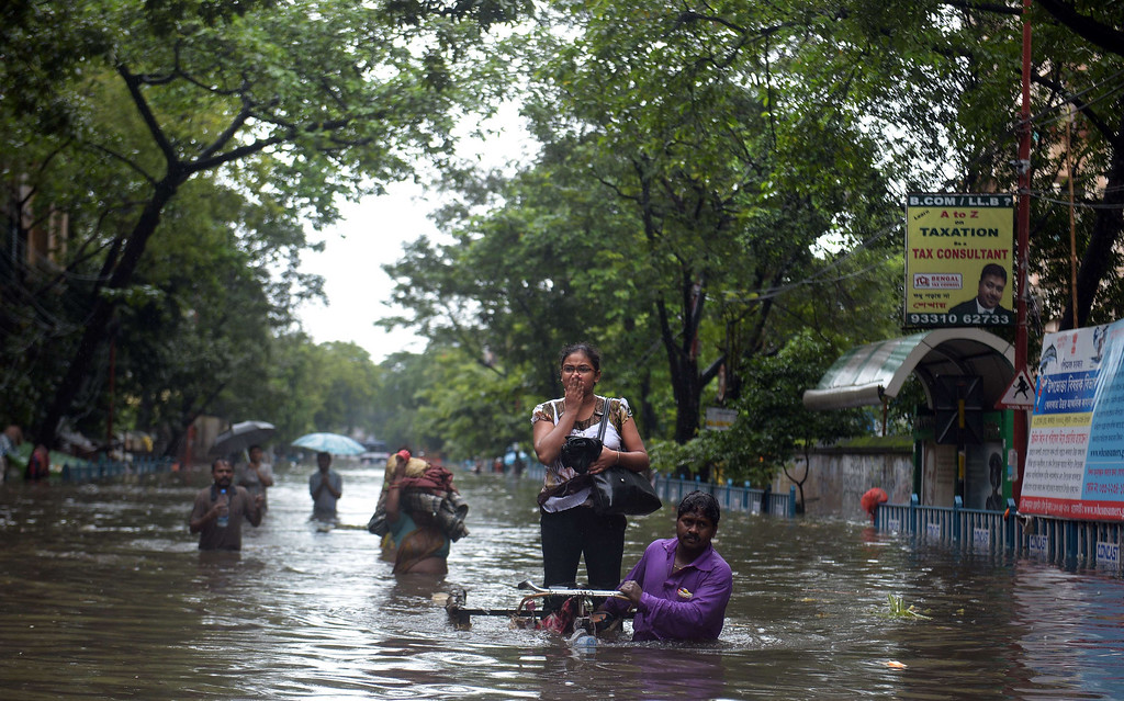 . An Indian rickshaw puller carries a student through water-logged streets in Kolkata on October 26, 2013.  Persistent rain for the last 24 hours has thrown normal life out of gear with reports of water logging at major arterial roads of the city which received 14 cm rainfall, the highest rainfall during the ongoing depression in eastern India. DIBYANGSHU SARKAR/AFP/Getty Images
