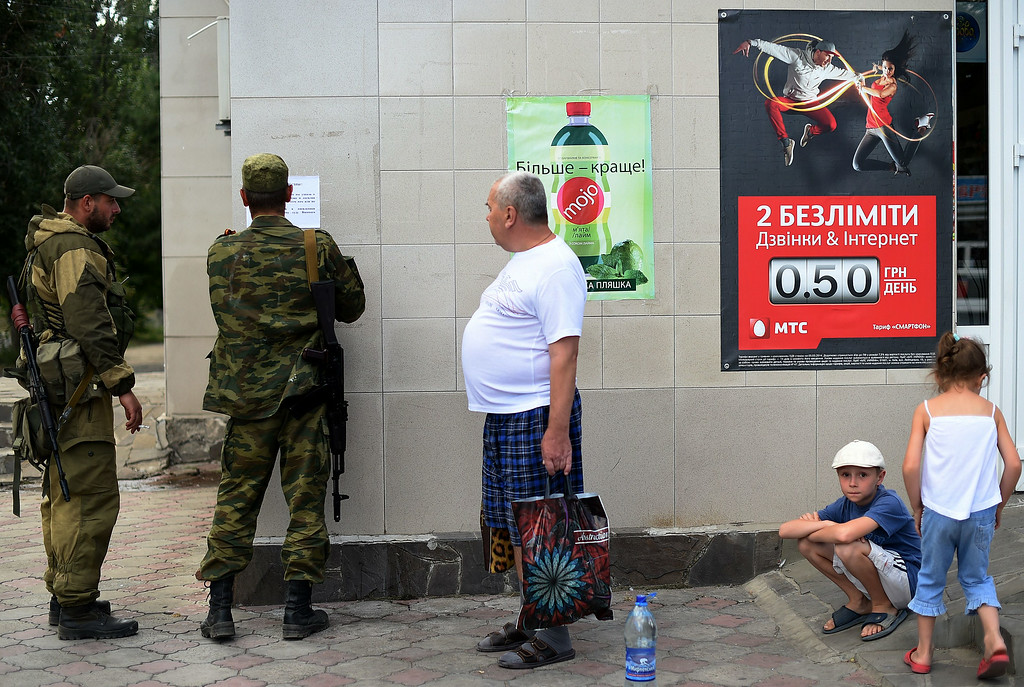 """. Villagers look at pro-Russian fighters pasting a paper on the wall of a supermarket in downtown Novoazovsk, 50kms east of the Ukrainian port city of Mariupol, on August 29, 2014. The paper reads\"""" The Fredom Army of Novarussia welcomes you, we are here and planning to stay for a long time. Do not believe in rumors that we are about to leave the city. Our goal is to go further, your goal is to build up a peaceful and honourable lifestyle\"""".  Residents in east Ukraine\'s strategic port Mariupol dug trenches Friday as others packed up and fled over fears the city could be the next target for advancing pro-Russian rebels. FRANCISCO LEONG/AFP/Getty Images"""