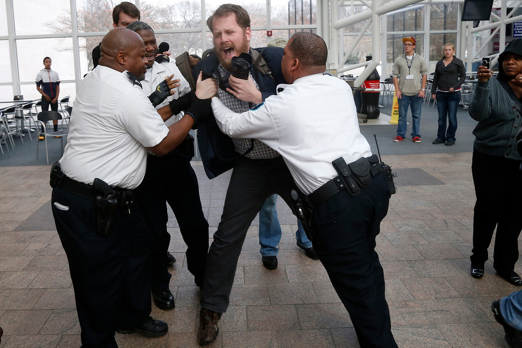 . Security guards grab freelance photojournalist Kristoffer Tripplaar to stop him from photographing a protest at a McDonald\'s restaurant inside the Smithsonian\'s National Air and Space Museum in Washington, Thursday, Dec. 5, 2013.=(AP Photo/Charles Dharapak)