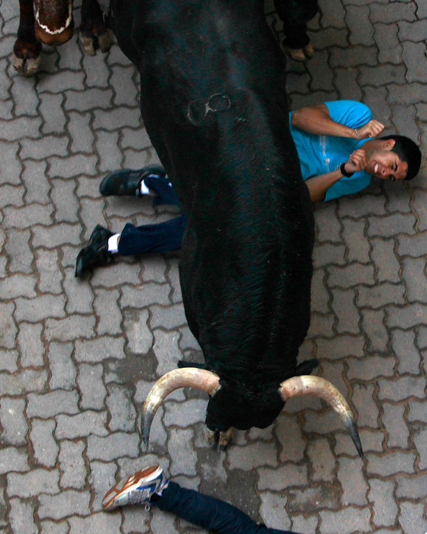 . A runner is knocked down by Valdefresno fighting bulls at the entrance to the bullring during the third running of the bulls of the San Fermin festival in Pamplona July 9, 2013. Two runners were treated in hospital for bruising following the run that lasted two minutes and twenty seven seconds, according to local media. REUTERS/Joseba Extaburu