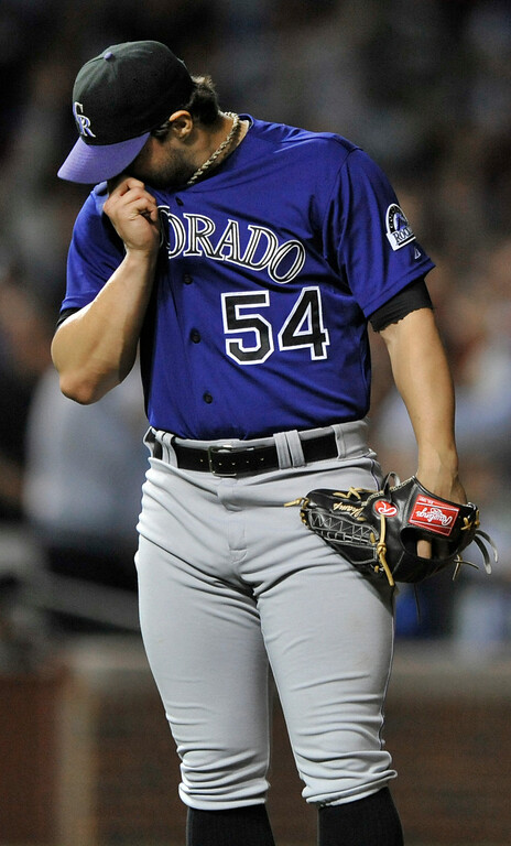 . Colorado Rockies relief pitcher Tommy Kahnle wipes his face after giving up a two-run home run to Chicago Cubs\' Luis Valbuena during the eighth inning of a baseball game in Chicago, Wednesday, July 30, 2014. (AP Photo/Paul Beaty)
