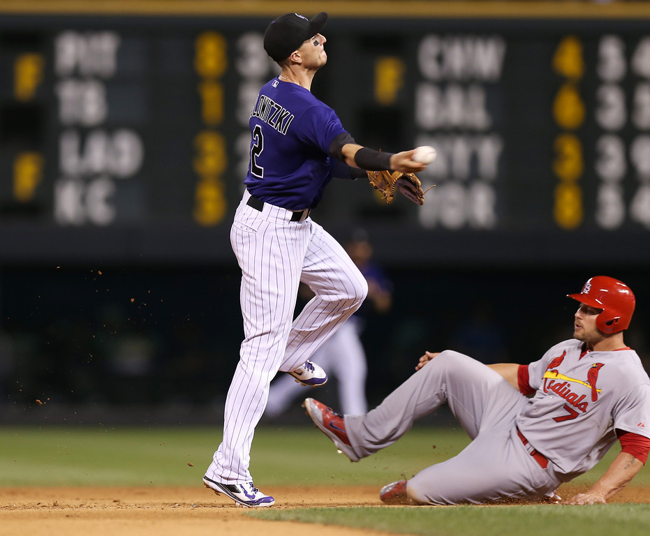 . Colorado Rockies shortstop Troy Tulowitzki, left, flies over St. Louis Cardinals\' Matt Holliday after forcing him out at second base on the front end of a double play hit into by Matt Adams to end the top of the eighth inning of the Cardinals\' 8-0 victory in a baseball game in Denver on Monday, June 23, 2014. (AP Photo/David Zalubowski)