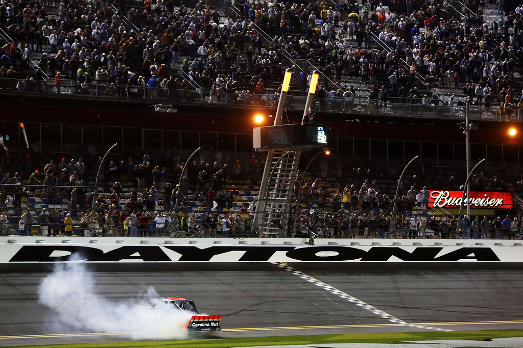 . DAYTONA BEACH, FL - FEBRUARY 22:  Johnny Sauter, driver of the #98 Carolina Nut Co./Curb Records Toyota, performs a burnout to celebrate winning the NASCAR Camping World Truck Series NextEra Energy Resources 250 at Daytona International Speedway on February 22, 2013 in Daytona Beach, Florida.  (Photo by Jerry Markland/Getty Images)