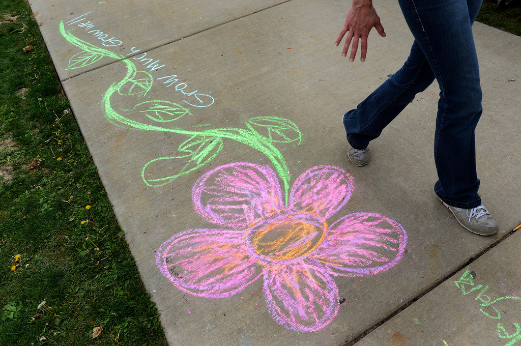 . AURORA, CO. - MAY 18: Children decorated the sidewalk with chalk art during the North Middle School Garden Festival in Aurora, CO May 18, 2013. The celebration marked the opening of the first school-based community garden in Aurora Public Schools. The project, funded by The Piton Foundation, was made possible through a partnership of Aurora Public Schools, Denver Urban Gardens (DUG), and Anschutz Medical Campus Department of Family Medicine and BRANCH, a multi-disciplinary student organization from the medical campus. A second garden is scheduled to open later this year at Hinkley High School. (Photo By Craig F. Walker/The Denver Post)