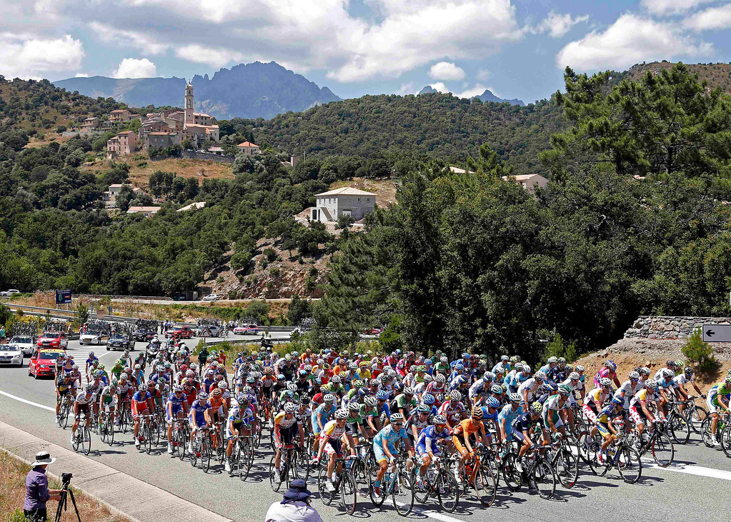 . The pack of riders cycles on its way past the village of Soveria during the 156 km second stage of the centenary Tour de France cycling race from Bastia to Ajaccio, on the French Mediterranean island of Corsica June 30, 2013.     REUTERS/Jean-Paul Pelissier