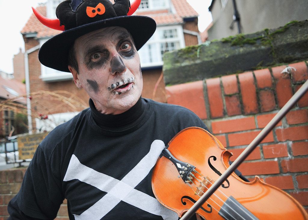 . WHITBY, ENGLAND - NOVEMBER 02: A street musician reacts to the camera as he entertains the crowds at the Goth weekend on November 2, 2013 in Whitby, England. The Whitby Gothic Weekend that takes place in the Yorkshire seaside town twice yearly in Spring and Autumn started in 1994 and sees thousands of extravagantly dressed followers of Victoriana, Steampunk, Cybergoth and Romanticism visit to take part in celebrating Gothic culture.  (Photo by Ian Forsyth/Getty Images)