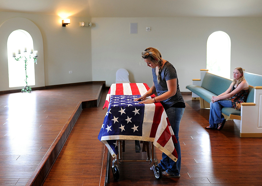 . Chantel Blunk, wife of Jonathan Blunk, cleans lint off the flag covering her husband\'s casket at Apollo and Three Tree Chapel in Littleton on Friday, July 27, 2012. Later that day, Blunk\'s body was flown to Reno, Nevada for his full military funeral. Blunk, a five-year U.S. Navy veteran, was killed during a July 20 shooting rampage at a movie theater in Aurora.